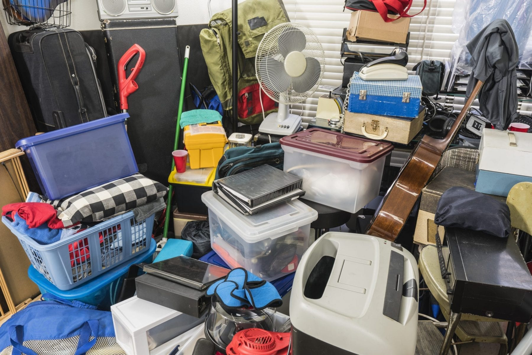 Home packed with stored boxes, vintage electronics, files, business equipment and household items.