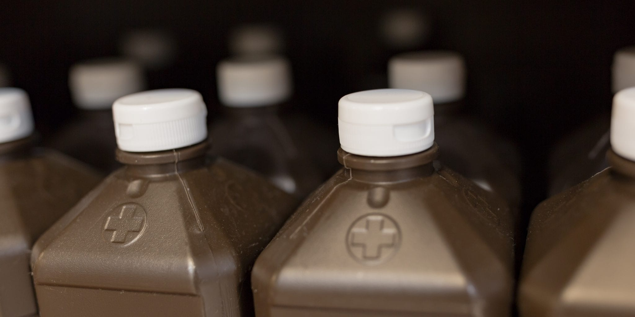 Close up of the tops of hydrogen peroxide brown bottles with white caps