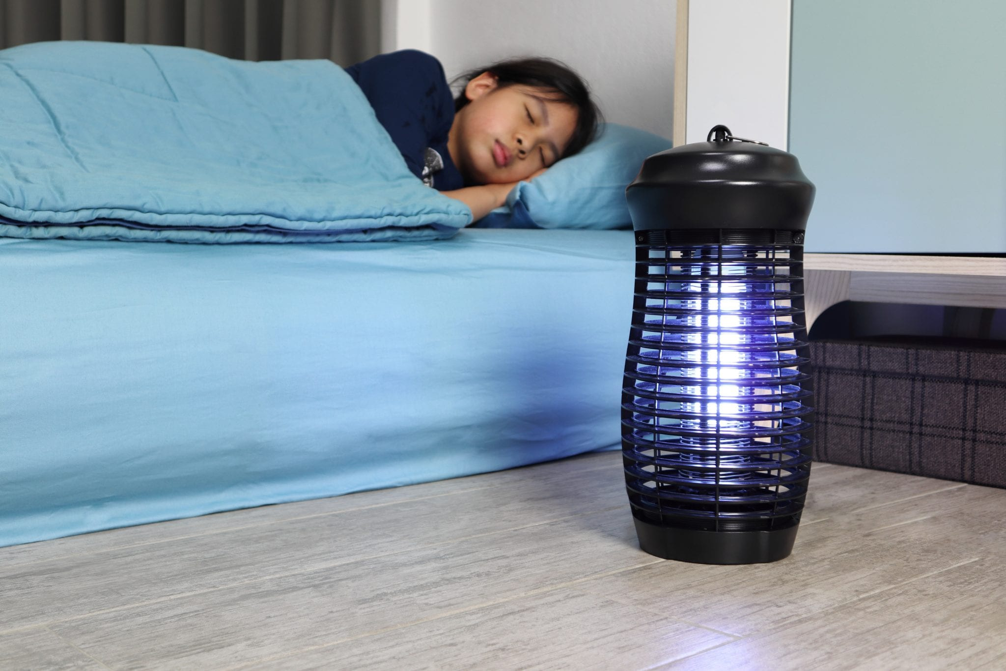 Child sleeping on mattress with blue sheets and bug zapper on the floor next to her