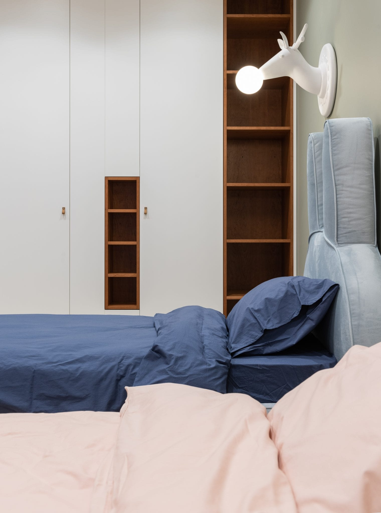 A twin bed with navy sheets and a twin bed with baby pink sheets are side by side in a bedroom with a deer shaped lamp.