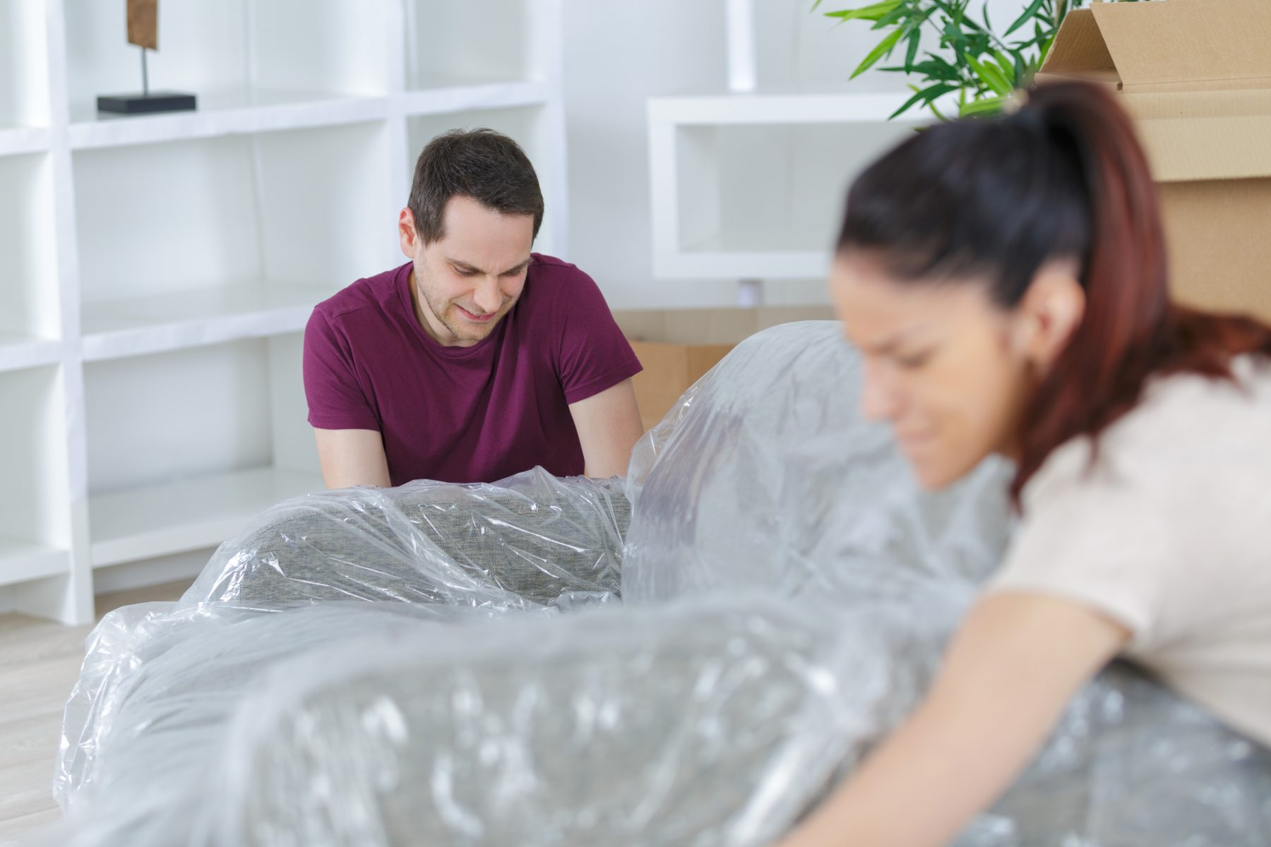 Couple moving a sofa wrapped in plastic.